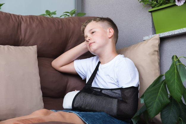Criança triste com um braço quebrado em ambiente doméstico elenco na mão de um menino