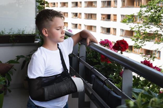 Criança triste com um braço quebrado engessado olha para o quintal da varanda