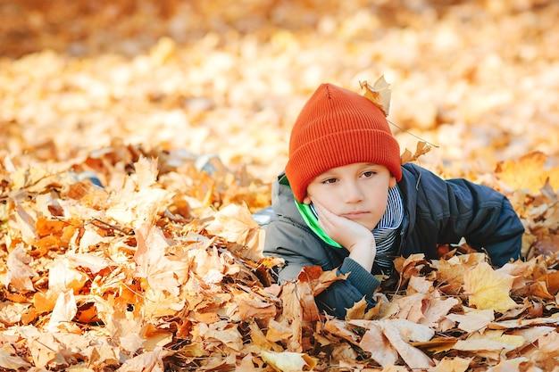 Criança triste descansando nas folhas de outono.