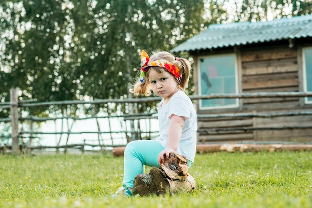Criança triste descontente e com raiva, menina sentada em cima do muro da aldeia. passeios no campo. agricultura.