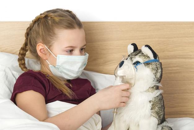 Criança triste doente em uma máscara com uma temperatura e uma dor de cabeça encontra-se na cama.