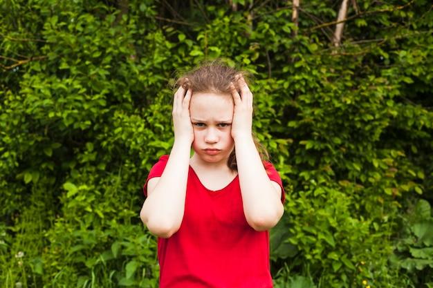Criança triste menina tendo dor de cabeça, olhando para a câmera em pé no parque