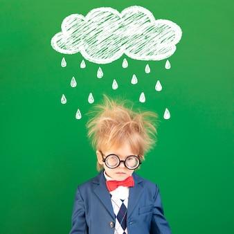 Criança triste nerd contra a lousa verde.
