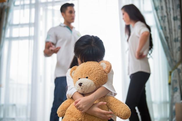 Criança triste por causa de seu pai e sua mãe discutindo