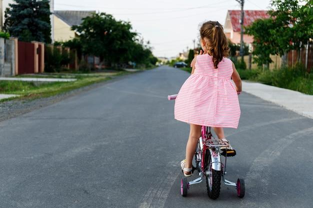 Criança, um, bicicleta, em, estrada asfalto