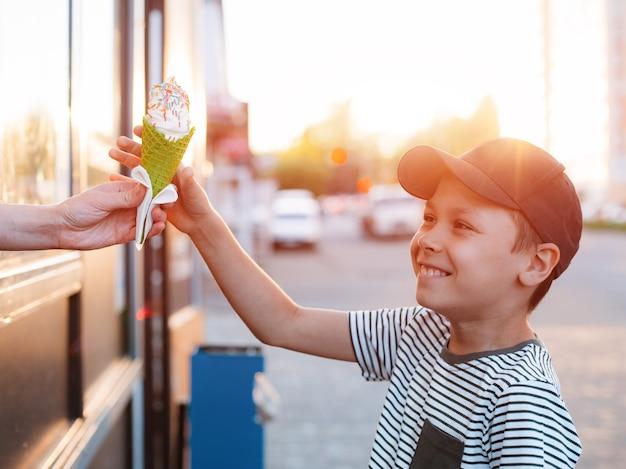 Criança, um garotinho compra sorvete em uma xícara de waffle verde na rua de uma sorveteira no calor do verão Foto Premium