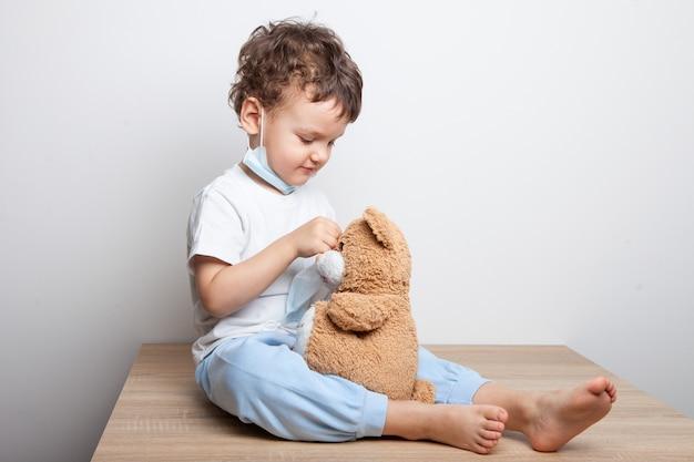 Criança, um menino com uma máscara médica coloca uma máscara em um ursinho de pelúcia.