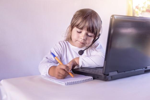 Criança uma menina em fones de ouvido com um microfone e um laptop escreve em um caderno em casa