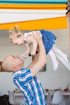 Criança usando aparelho auditivo em casa e brincando com o pai