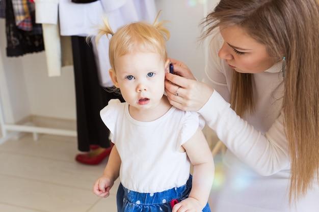 Criança usando aparelho auditivo em casa
