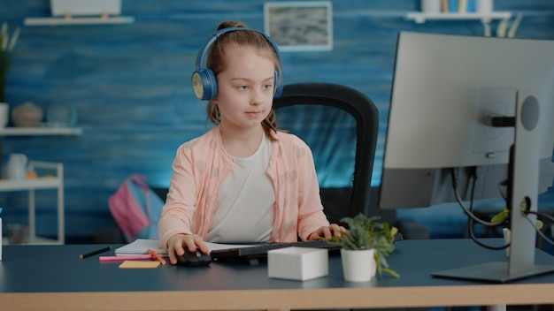 Criança usando fones de ouvido e desenhando no livro didático