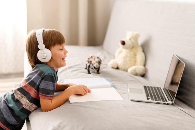 Criança usando fones de ouvido interações com a escola online