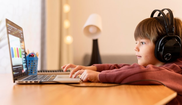 Criança usando fones de ouvido na escola virtual