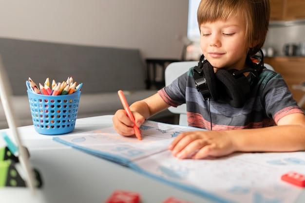 Criança usando fones de ouvido, participando de cursos online