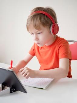 Criança usando fones de ouvido tentando entender a lição
