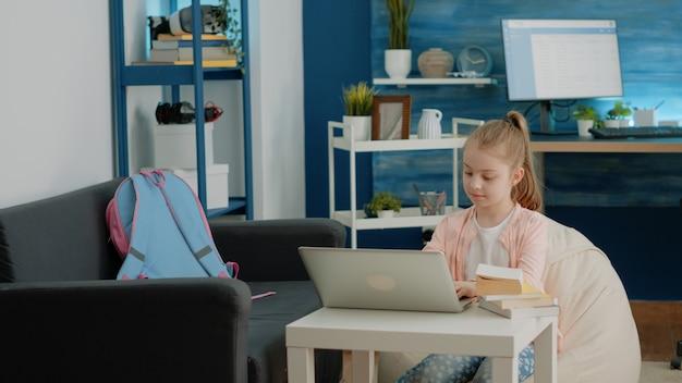 Criança usando laptop para aulas online em casa