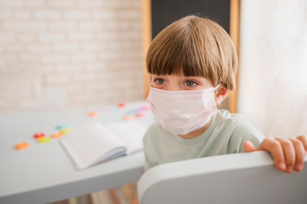 Criança usando máscara médica e sendo orientada em casa