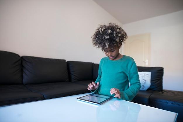 Criança usando tablet em casa Foto gratuita