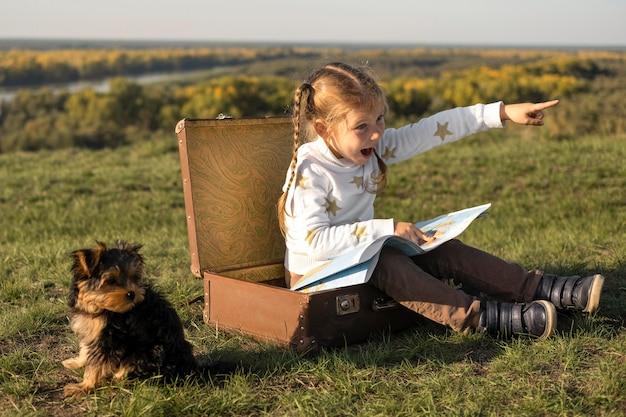 Criança usando um mapa e um cachorro sentado ao lado dela