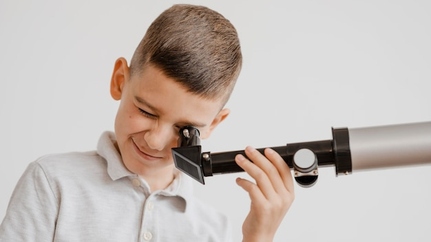 Criança usando um telescópio na aula