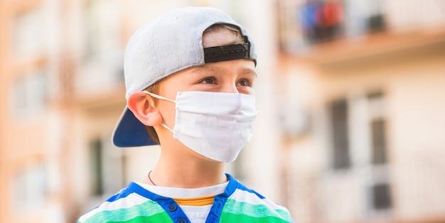 Criança usando uma máscara de medicamento ao ar livre. epidemia do coronavírus. menino com máscara de proteção. menino em uma bandagem cirúrgica. rapaz com uma máscara médica. quarentena e vírus de proteção.