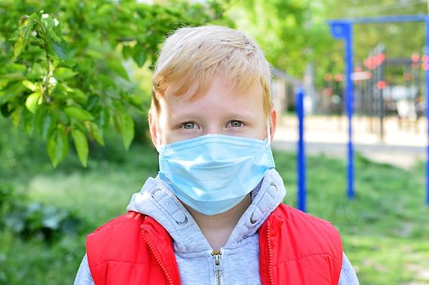 Criança usando uma máscara no parque. máscara facial para proteção contra surto de coronavírus. epidemia do coronavírus