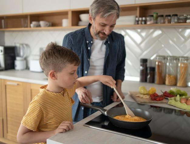 Criança vendo pai cozinhar omelete