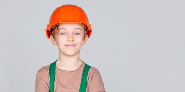 Criança vestida como um construtor operário. menino usando capacete. pequeno construtor de retrato em capacetes. capacete de construção infantil, capacete. pequeno construtor de capacete
