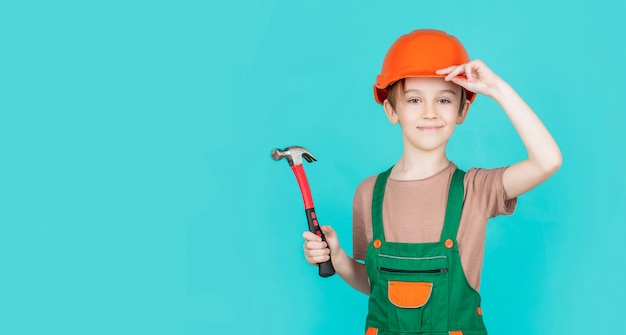 Criança vestida como um construtor operário. menino usando capacete. pequeno construtor de retrato no martelo de capacetes. capacete de construção infantil, capacete. martelo de martelo