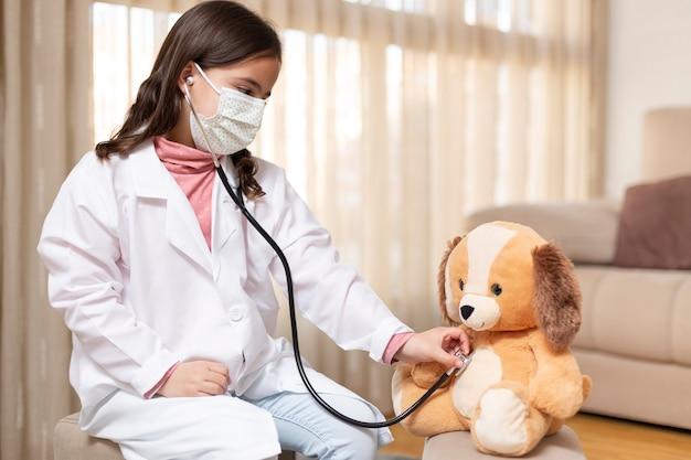 Criança vestida de médico examinando um ursinho de pelúcia com um estetoscópio