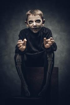 Criança vestida e maquiada como um esqueleto para a festa de halloween
