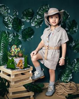 Criança vestida no estilo de um caçador de tesouros da selva com um chapéu e um bolo de dinossauro