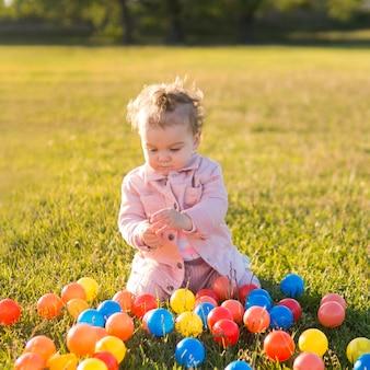 Criança vestindo roupas cor de rosa, brincando com bolas de plástico