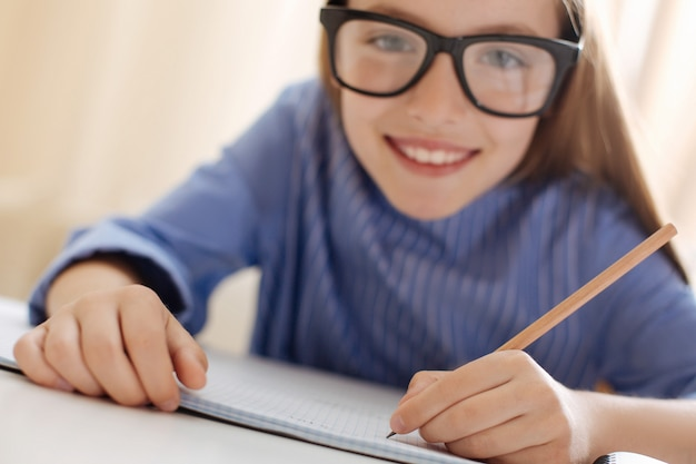 Criança vibrante e produtiva, sendo uma estudante diligente e trabalhando em sua tarefa enquanto faz algumas anotações em seu caderno