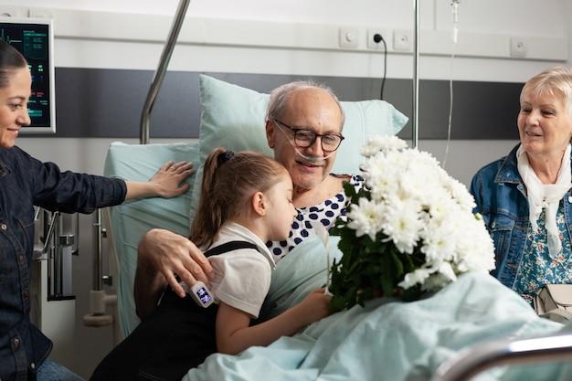 Criança visitando o avô idoso doente, apoiando-o após cirurgia médica