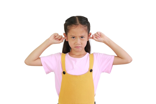 Criança zangada perto plug orelhas gritar alto cansado por som barulhento, furioso com raiva. menina asiática irritada isolada no fundo branco. criança evita ignorar ruídos altos insuportáveis pergunte em silêncio