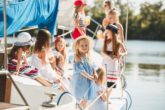 Crianças a bordo do iate do mar bebendo suco de laranja. meninas adolescentes ou crianças contra o céu azul ao ar livre.