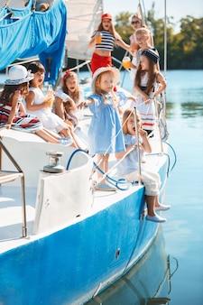 Crianças a bordo do iate do mar bebendo suco de laranja.