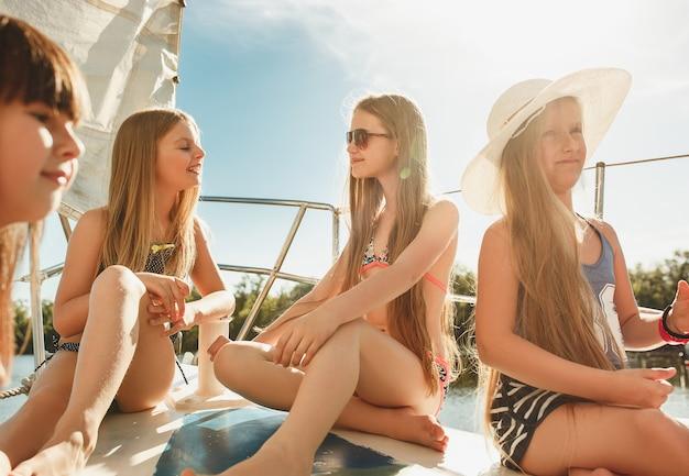 Crianças a bordo do iate do mar. meninas adolescentes ou crianças contra o céu azul ao ar livre