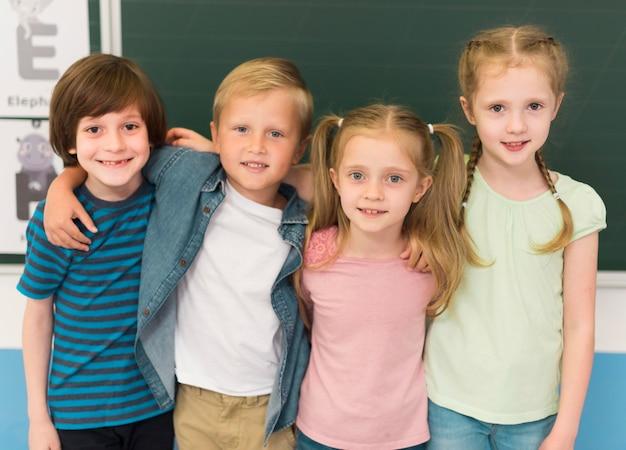 Crianças abraçadas na sala de aula