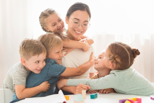 Crianças abraçando a professora