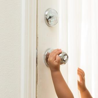 Crianças abrem a maçaneta da porta