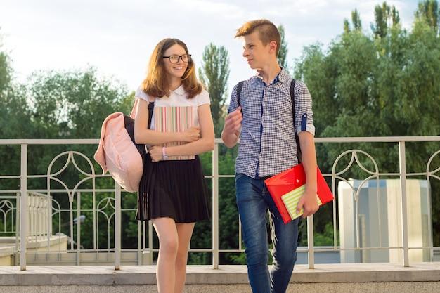 Crianças adolescentes com mochilas, livros didáticos