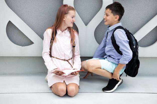 Crianças adolescentes escolares menino e menina no fundo da parede de concreto, crianças rindo com ...