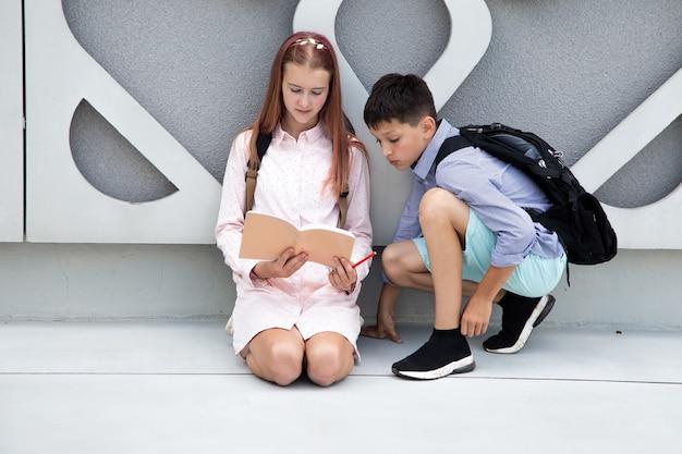 Crianças adolescentes escolares menino e menina no fundo da parede de concreto que a menina está fazendo em casa ...