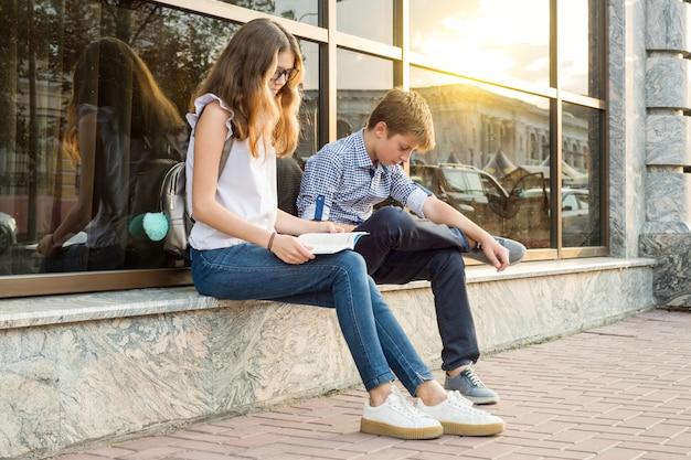Crianças adolescentes lendo livro e usando smartphone