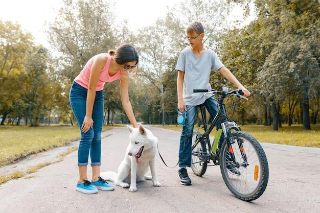 Crianças adolescentes na estrada no parque com cachorro branco husky