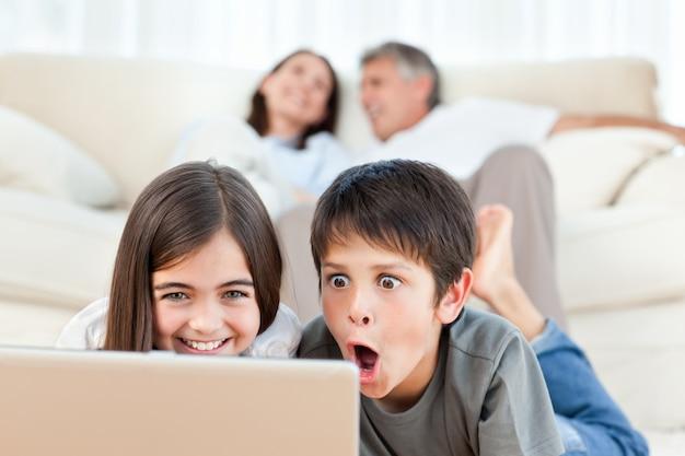 Crianças adoráveis assistindo um filme em seu laptop em casa