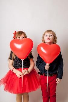 Crianças adoráveis com balão em forma de coração, sorrindo para a câmera isolada no branco