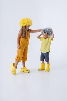 Crianças adoráveis de perucas se divertindo no estúdio